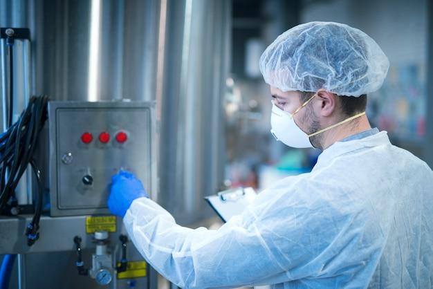 Technolog w mundurze ochronnym działającym w fabrycznej linii produkcyjnej