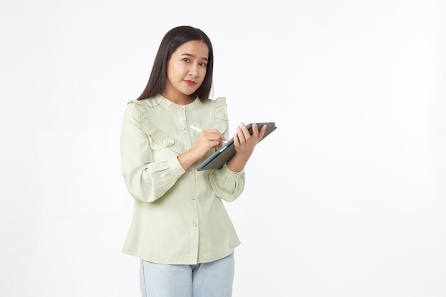 Technologia bezprzewodowa. piękna młoda kobieta azji trzymając cyfrowy tablet i patrząc na kamery z uśmiechem, stojąc na białym tle.