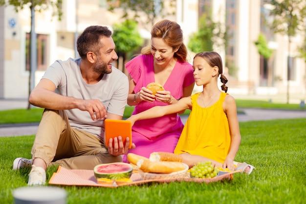 Technologia cyfrowa. szczęśliwy miły mężczyzna trzyma nowoczesny tablet, pokazując go swojej córce i żonie