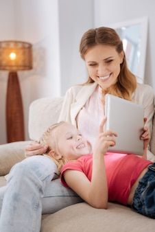 Technologia cyfrowa. wesoła, zachwycona młoda dziewczyna, leżąc na kolanach matki i patrząc na ekran tabletu, odpoczywając w domu