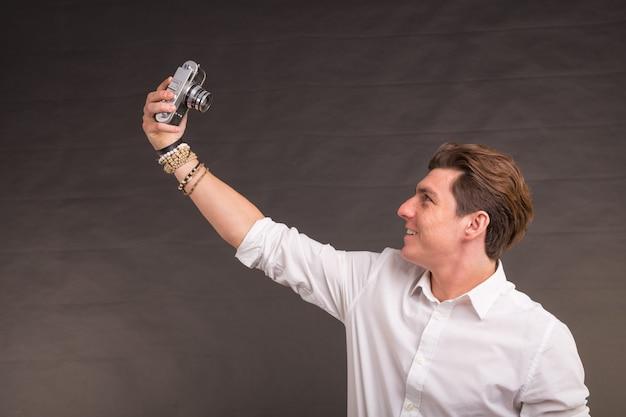 Technologia, fotografia i ludzie pojmują - przystojny mężczyzna w białej koszuli robi sobie selfie