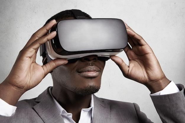 Technologia i rozrywka. odnoszący sukcesy ciemnoskóry pracownik biurowy w eleganckim szarym garniturze doświadczający wirtualnej rzeczywistości przy użyciu okularów vr.