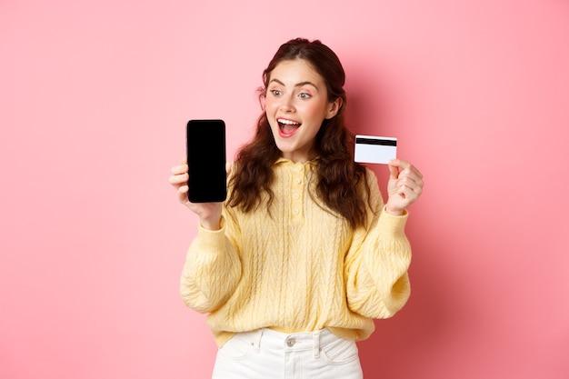Technologia i zakupy online. podekscytowana atrakcyjna dziewczyna pokazuje ekran smartfona, plastikową kartę kredytową, patrzy zdziwiona na telefon, stojąc przed różową ścianą.