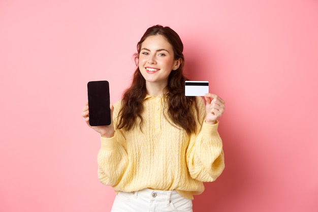Technologia i zakupy online. portret pięknej pani pokazującej ekran telefonu komórkowego i plastikową kartę kredytową, uśmiechnięta zadowolona, polecająca aplikację, stojąca nad różową ścianą.