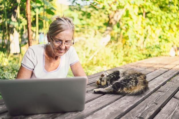 Technologia, koncepcja ludzi w podeszłym wieku - starsza szczęśliwa starsza kobieta z kotem domowym, pracująca online z laptopem na zewnątrz w ogrodzie. praca zdalna, edukacja na odległość.