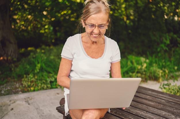 Technologia, koncepcja osób starszych - osoby starsze szczęśliwy starszy starsza kobieta pracuje online z laptopa na zewnątrz w ogrodzie. praca zdalna, edukacja na odległość.