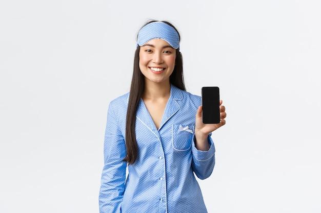 Technologia, ludzie i koncepcja wypoczynku w domu. szczęśliwa uśmiechnięta azjatka w piżamie i masce do spania, śledząca swój sen za pomocą aplikacji mobilnej, pokazująca ekran smartfona i wyglądający na zadowolonego, białe tło.