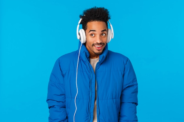 Technologia, nowoczesny styl życia i koncepcja gadżetów. rozochocony atrakcyjny modnisia amerykanina afrykańskiego pochodzenia facet chodzi zima śnieżne ulice, jest ubranym wyściełaną kurtkę i słuchawki, słucha muzyki