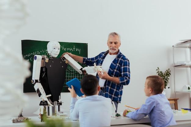 Technologia przyszłości. pozytywnie starzejący się mężczyzna patrząc na swoich uczniów, opowiadając im o robotach