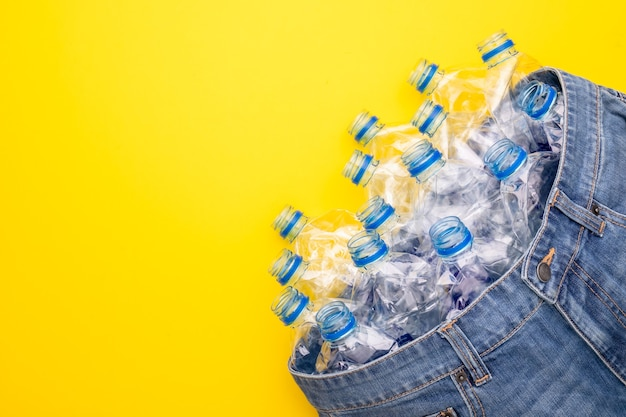 Technologia recyklingu plastikowych butelek do produkcji ubrań. widok z góry na starą butelkę wody i niebieskie krótkie dżinsy