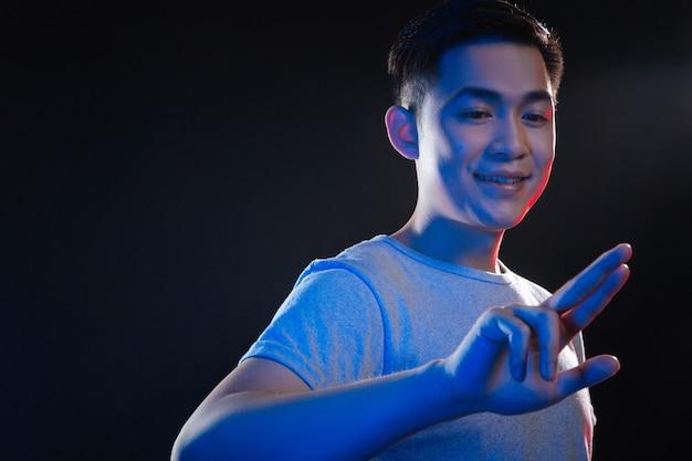 Technologia sensoryczna. wesoły szczęśliwy człowiek patrząc na jego rękę, naciskając sensor
