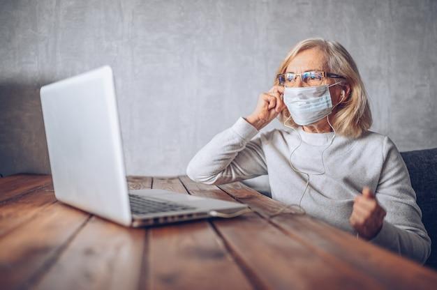 Technologia, starość i ludzie pojęć - osamotniona smutna starsza starsza kobieta w twarzy medycznej masce pracuje i robi rozmowę wideo z laptopem w domu podczas koronawirusa covid19 pandemii. zostań w domu