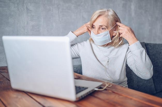 Technologia, starość i ludzie pojęć, - starsza starsza kobieta z twarzy medyczną maską pracuje i robi rozmowie wideo z laptopem w domu podczas koronawirusa covid19 pandemii. koncepcja pobytu w domu