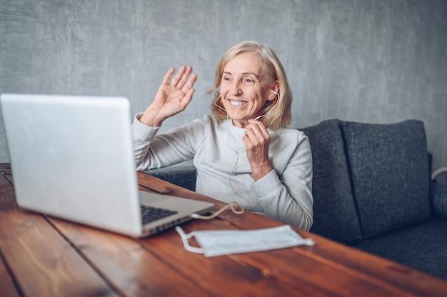 Technologia, starość i ludzie pojęć, - szczęśliwa starsza starsza kobieta z twarzy medyczną maską pracuje rozmowę wideo z laptopem w domu podczas coronavirus covid19 i robi rozmowie telefonicznej. zostań w domu