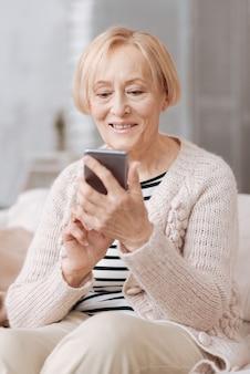 Technologia uczenia się. jasna, wesoła dojrzała kobieta, siedząc na kanapie w domu, rozmawiając z przyjaciółmi za pośrednictwem mediów społecznościowych
