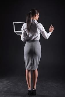 Technologia w biznesie. profesjonalna ładna atrakcyjna bizneswoman trzyma laptopa i patrząc na jej palec podczas korzystania z nowoczesnych technologii w swojej pracy