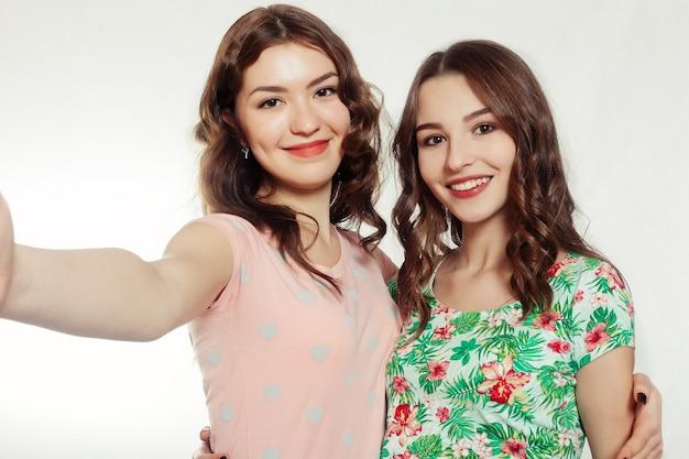 Technologie, emocje, styl życia, ludzie, nastolatki i koncepcja przyjaźni - ładne nastolatki lub przyjaciółki robią sobie selfie na szarym tle