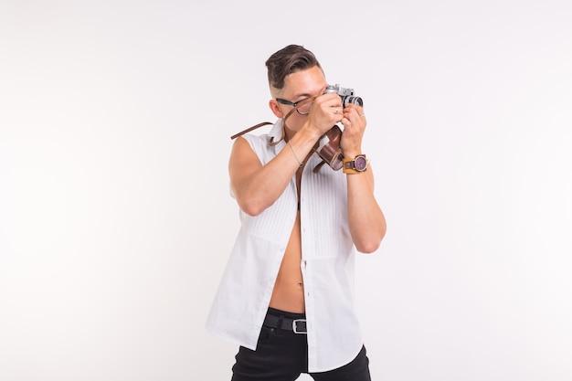 Technologie, fotografowanie i koncepcja ludzi - przystojny młody człowiek z aparatem retro na białej powierzchni