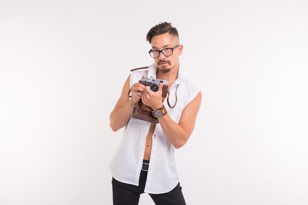 Technologie, fotografowanie i koncepcja ludzi - przystojny młody człowiek z aparatem retro na białym tle.