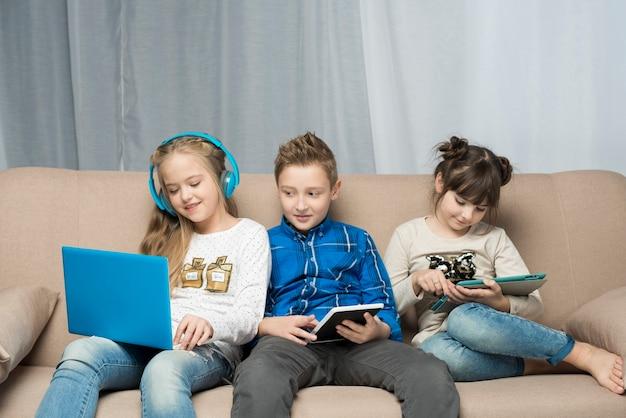 Technologii pojęcie z trzy dzieciakami na kanapie