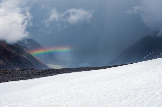 Tęcza nad doliną góry zima śnieg. klimatyczny krajobraz alpejski z ośnieżonymi górami z tęczą w deszczową i słoneczną pogodę.