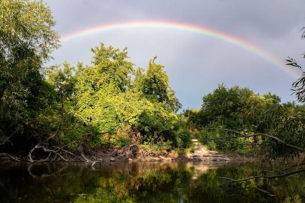 Tęcza nad rzeką w zielonym lesie. idylliczny krajobraz