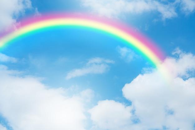 Tęcza w niebieskim niebie z chmurami