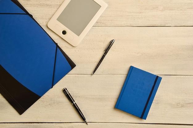 Teczka na dokumenty, elektroniczna książka, dwa długopisy i notes leżą na drewnianym beżowym stole