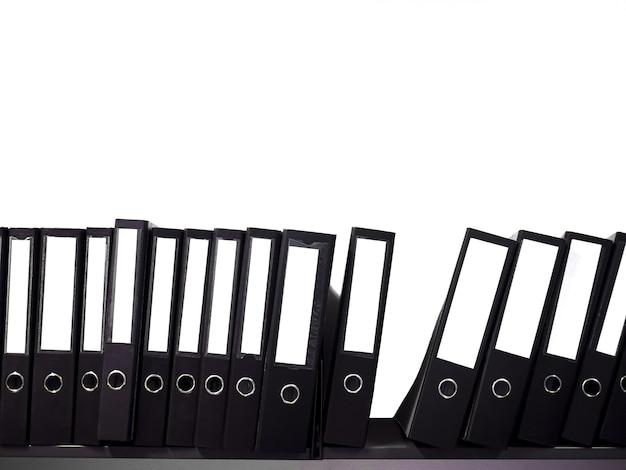 Teczka z dokumentami w kolorze czarnym i pusty grzbiet książki ułożone są na półkach