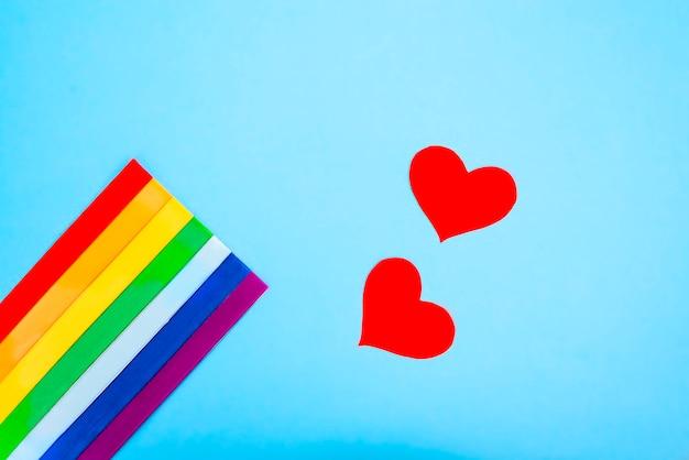 Tęczowa flaga lgbt i czerwone serce na niebieskim tle. koncepcja lgbt. symbol ruchu lgbt