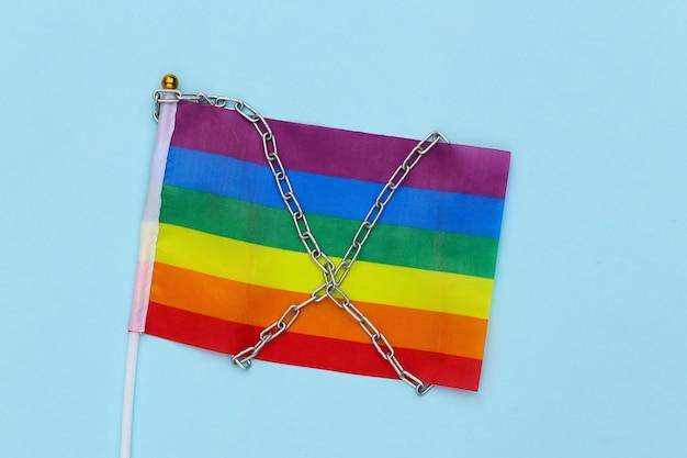 Tęczowa flaga lgbt owinięta stalowym łańcuszkiem. nietolerancja
