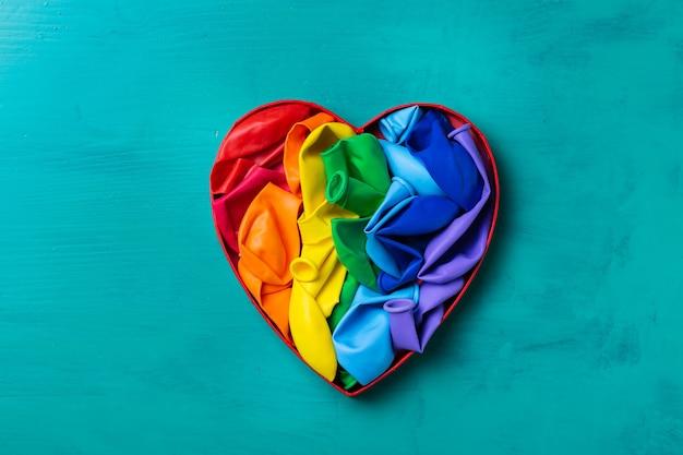 Tęczowa flaga lgbtq w kształcie serca na turkusowym tle dumy miesiąca