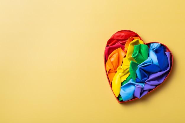 Tęczowa flaga lgbtq w kształcie serca na żółtym tle duma miesiąca