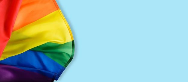 Tęczowa flaga na jasnoniebieskim tle, międzynarodowy symbol społeczności lgbt widok z góry. baner, miejsce na kopię.