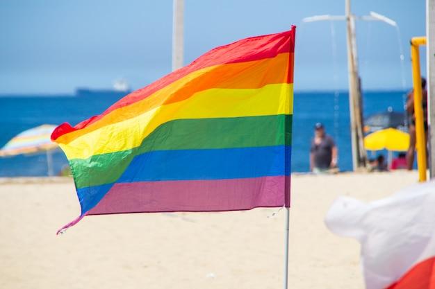 Tęczowa flaga używana przez społeczeństwo lgbt na plaży copacabana w rio de janeiro.