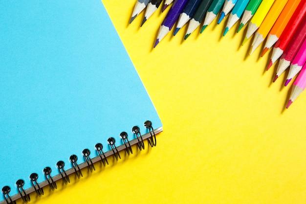 Tęczowa paleta kolorowych kredek z notesem spiralnym na żółtym tle, powrót do szkoły, lekcje rysunku.