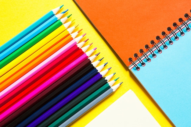Tęczowa paleta kolorowych ołówków z notesem spiralnym na żółtym tle