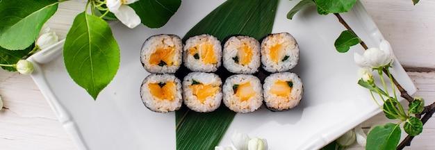 Tęczowa rolka sushi z łososiem tuńczykiem awokado krewetka królewska serek philadelphia kawior tobica chuka sushi menu japońskie jedzenie wysokiej jakości zdjęcie
