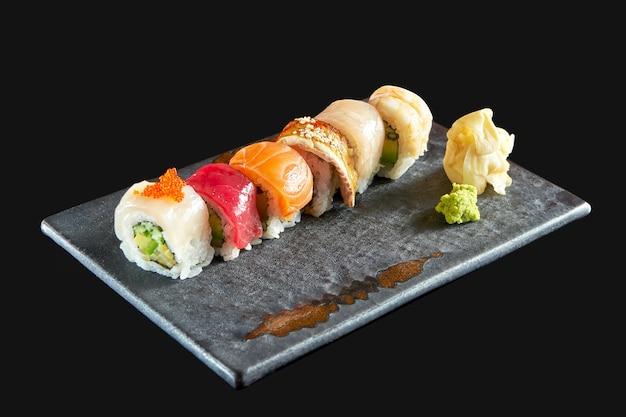Tęczowa rolka sushi z różnymi rodzajami owoców morza: łososiem, węgorzem, krewetkami, przegrzebkami, tuńczykiem i awokado, podana na ceramicznym talerzu z imbirem i wasabi. pojedynczo na czarnym tle. japońskie jedzenie