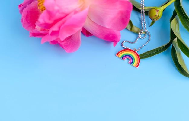 Tęczowa zawieszka jako symbol lgbt i różowa piwonia na niebieskim tle