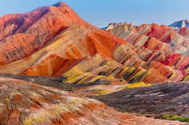 Tęczowe góry i tło błękitnego nieba w zachód słońca. narodowy geopark zhangye danxia, gansu, chiny. kolorowy krajobraz, tęczowe wzgórza