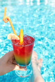 Tęczowy koktajl z lodem w żeńskiej ręce przy basenie.