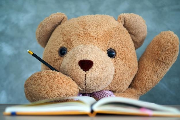 Teddy bear siedzi na biurku i podnieś rękę, gdy zostaniesz o to poproszony.