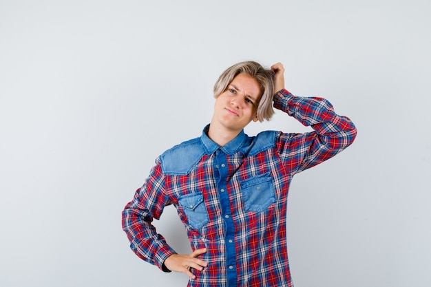 Teen chłopiec drapiąc się po głowie, patrząc na bok w kraciastej koszuli i patrząc zamyślony. przedni widok.