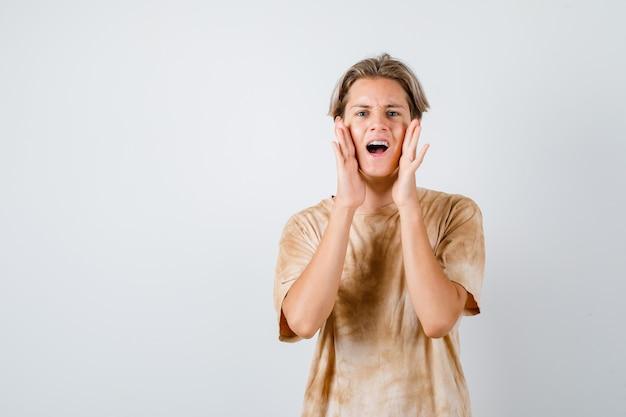 Teen chłopiec krzyczy trzymając ręce w pobliżu ust w koszulce i patrząc zmartwiony. przedni widok.