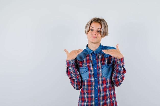 Teen chłopiec pokazując gest wysokości w kraciastej koszuli i patrząc radosny. przedni widok.