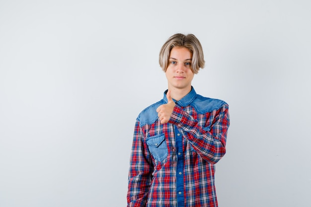 Teen chłopiec pokazując kciuk w kraciaste koszule i patrząc zadowolony, widok z przodu.