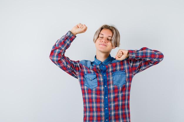 Teen chłopiec rozciąganie górnej części ciała w kraciastej koszuli i wyglądający na zrelaksowany. przedni widok.
