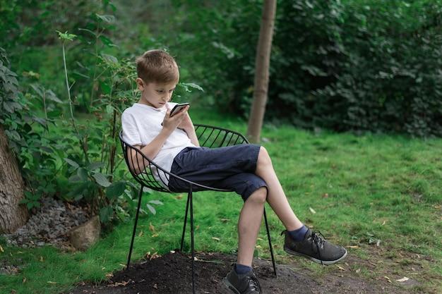 Teen chłopiec siedzi na krześle na charakter i patrząc na telefon. gadżety współczesnego człowieka