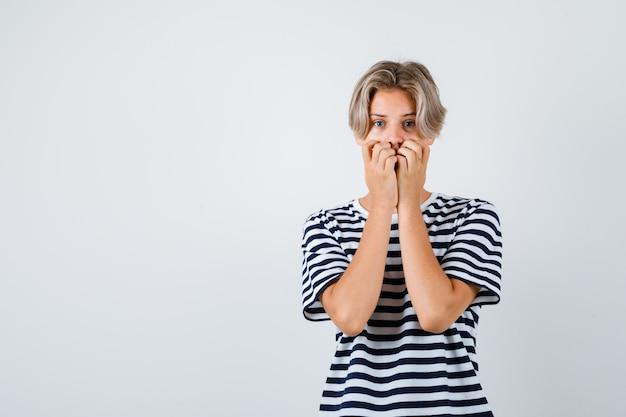 Teen chłopiec trzymając ręce na twarzy w t-shirt i patrząc przestraszony, widok z przodu.